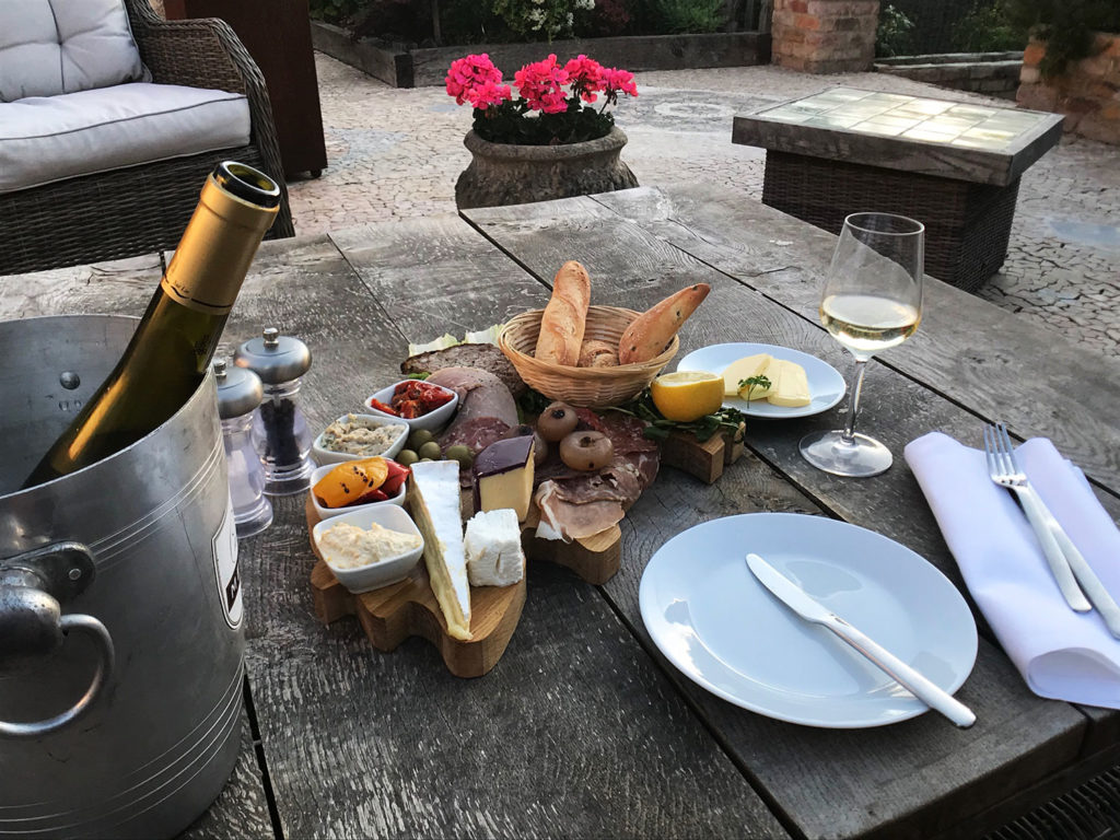 A platter on the patio & a glass of chilled Pinot at Piglets Boutique B&B